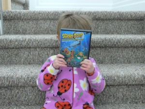 """And the winner is...""  (She's not listening anyhow.  I think she's reading the blurb on the back of the Scooby case!)"