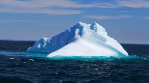 An iceberg is frozen glacial (fresh) water.  As it melts, a bright turquoise puddle of fresh water appears around the iceberg in the surrounding salty ocean.