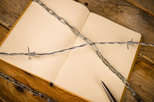 60263773 - notebook and pen  with barbed wire, a press censorship concept